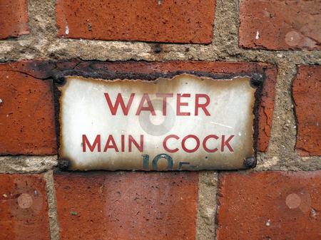 Water cock wall stock photo, Red brick wall with aged water mains sign that has rusted by Michael Travers