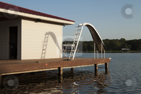 Slide stock photo, A waterslide on the end of a wooden dock by Kevin Tietz