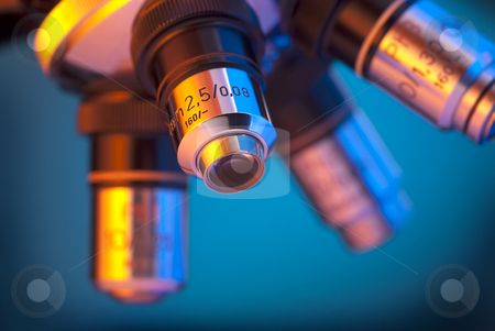Microscope lens turret stock photo, Microscope four lens turret in blue by Christian Delbert