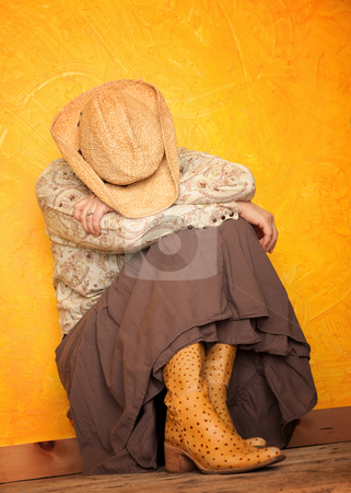 Western woman with her head down stock photo, Pretty western woman in cowboy shirt and hat with her head down by Scott Griessel