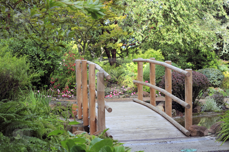 Wood Bridge Over Water stock photo, Small crossing above a stream in a beautiful landscaped park. by Lee Serenethos