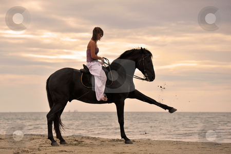 Girl and  horse on the beach stock photo, Beautiful black stallion on the beach with young woman by Bonzami Emmanuelle