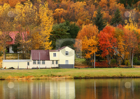 End of summer stock photo, An old house in autumn, leaves in vivid color, reflecting in water. by Johann Helgason