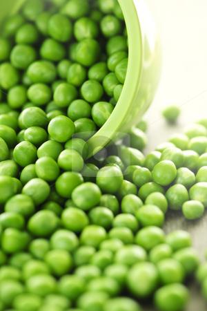 Spilled bowl of green peas stock photo, Closeup on spilling bowl of fresh green green peas by Elena Elisseeva