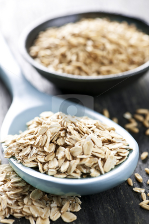 Rolled oats and oat groats stock photo, Rolled oats heaped on a spoon and whole oat groats by Elena Elisseeva