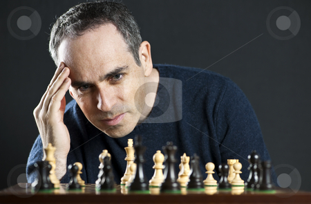 Man playing chess stock photo, Chessboard with man thinking about chess strategy by Elena Elisseeva