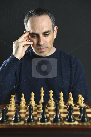Man playing chess stock photo, Man looking at wooden chess board thinking about first move by Elena Elisseeva