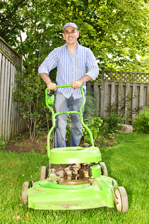 Man mowing lawn stock photo, Man with lawn mower in landscaped backyard by Elena Elisseeva