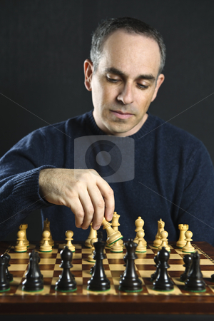 Man playing chess stock photo, Man moving a chess piece on wooden chessboard by Elena Elisseeva
