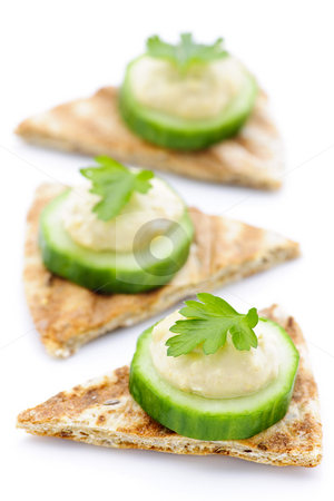 Appetizer of pita with hummus and cucumber stock photo, Appetizer of hummus and cucumber slices on pita bread by Elena Elisseeva