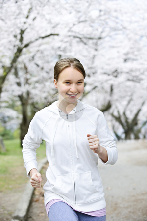Girl jogging in park stock photo, Beautiful teenage girl jogging in park with blooming apple trees by Elena Elisseeva