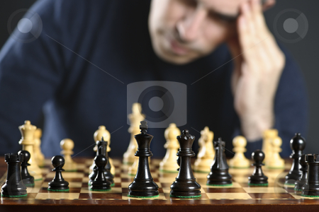 Man at chess board stock photo, Chessboard with man thinking about chess strategy by Elena Elisseeva