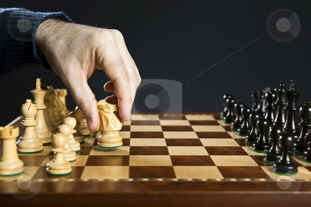 Hand moving knight on chess board stock photo, Hand moving a knight chess piece on wooden chessboard by Elena Elisseeva