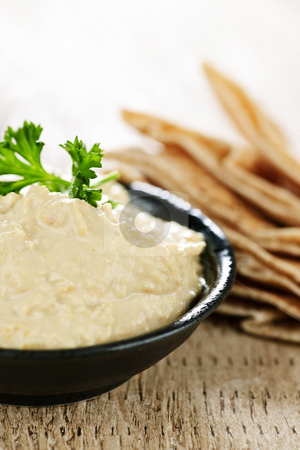 Hummus with pita bread stock photo, Bowl of fresh hummus dip with pita bread slices by Elena Elisseeva