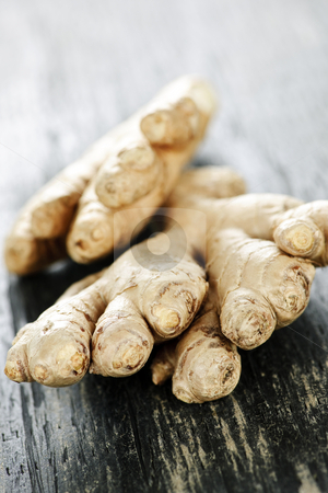 Ginger root stock photo, Close up of fresh ginger root spice on wooden table by Elena Elisseeva