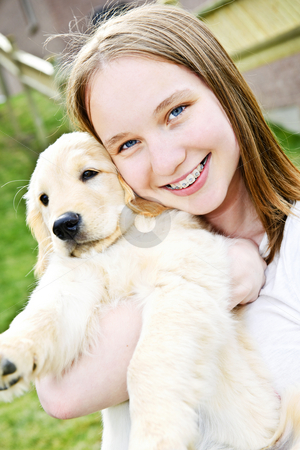 Girl with puppy stock photo, Portrait of smiling teenage girl holding golden retriever puppy by Elena Elisseeva