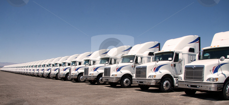 Semi Truck Fleet stock photo, Semi truck fleet lined up in a row with copy space by Gunter Nezhoda