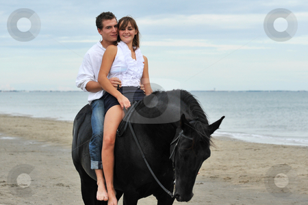 Couple and  horse on the beach stock photo, Beautiful black stallion on the beach with young couple by Bonzami Emmanuelle