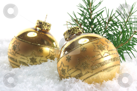 Christmas balls stock photo, Two golden Christmas balls with pine branches lying in the snow by Marén Wischnewski