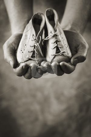 First shoes stock photo, Dirty hands holding a pair of baby shoes. Very shallow depth of field. by Stocksnapper