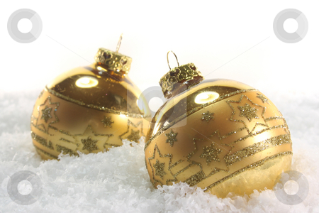Christmas balls stock photo, Two golden Christmas balls lying in the snow by Marén Wischnewski