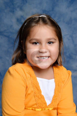Kindergarten Girl Portrait stock photo, A smiling young girl portrait with a blue background by Richard Nelson
