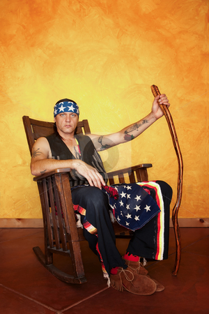 Native American man stock photo, Kneeling Native American man in rocking chair by Scott Griessel