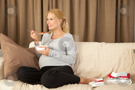 Healthy pregnancy stock photo, Beautiful pregnant woman looking happy and holding a bowl of healthy food by Simone Van den Berg