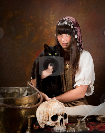 Young witch with black cat stock photo, Halloween witch holding her black cat with green eyes (the book is 300 years old, no copyright problems) by Anneke