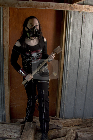 Axe murderer stock photo, Twenty something girl dress in goth fashion with a axe in front of a wooden door by Yann Poirier