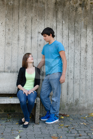Teen Couple stock photo, A young teen girl is sitting on a bench while staring up at her boyfriend by Richard Nelson