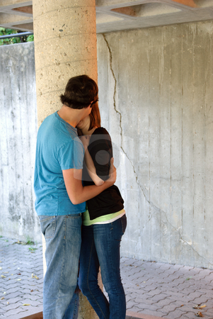 Teenagers Kissing stock photo, A teenage couple are kissing by a stone pillar outside by Richard Nelson