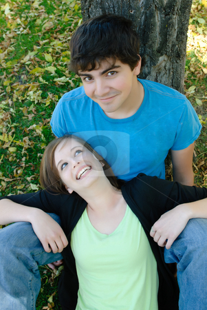Smiling Teen Couple stock photo, A smiling teen couple are sitting on the ground by a tree by Richard Nelson