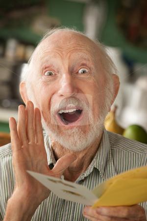 Senior man with greeting card stock photo, Senior man at home reading greeting card by Scott Griessel