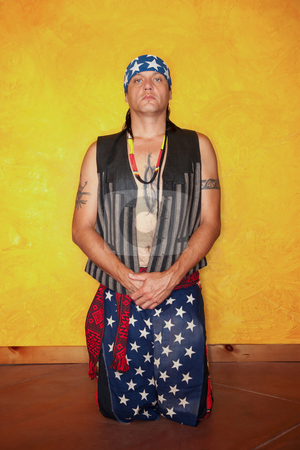 Kneeling Native American man stock photo, Kneeling Native American man with tattoos and vest by Scott Griessel