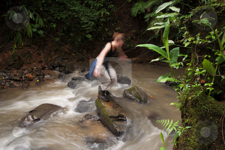 Woman crossing a river in Costa Rica stock photo, Adventurous woman crossing a river in Costa Rica by Scott Griessel