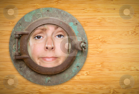 Antique Porthole on Bamboo Wall with Funky Woman Looking Through stock photo, Antique Porthole on Bamboo Wall with Funky Woman Looking Through the Window. by Andy Dean