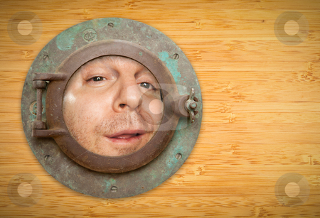 Antique Porthole on Bamboo Wall with Funky Man Looking Through stock photo, Antique Porthole on Bamboo Wall with Funky Man Looking Through the Window. by Andy Dean