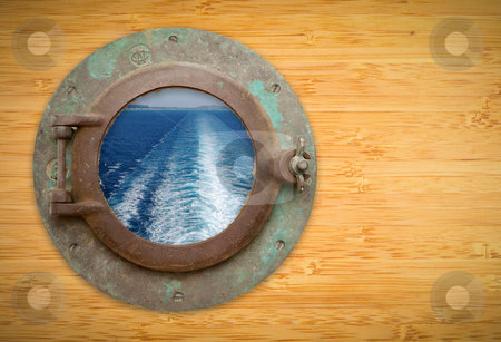Antique Porthole on Bamboo Wall with View of Ship Ocean Trail stock photo, Antique Porthole on Bamboo Wall with View of Ship Wave Trail, Land and Sky. by Andy Dean