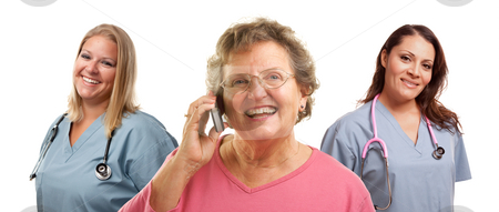Senior Woman Using Cell Phone and Female Doctors Behind stock photo, Happy Senior Woman Using Cell Phone with Female Doctors or Nurses Behind Isolated on a White Background. by Andy Dean