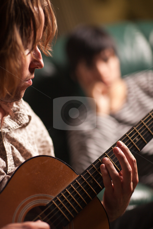 Young Musician Plays His Acoustic Guitar as Friend Listens stock photo, Young Musician Plays His Acoustic Guitar as Friend in the Background Listens. by Andy Dean