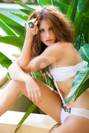 Attractive Young Woman Posing in a Designer Swimsuit stock photo, Beautiful young woman sits on a wall and poses with her hand in her hair. by Angela Hawkey