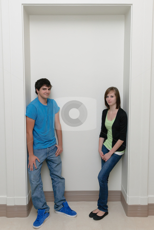 Two Teenagers stock photo, Two teenagers leaning  in an alcove with copyspace above. by Richard Nelson