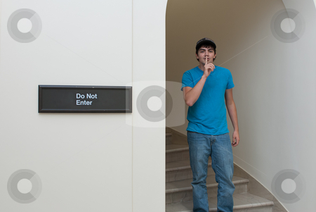 Sneaking Teen stock photo, A teenage boy is sneaking into an area that he isn't supposed to go to. by Richard Nelson