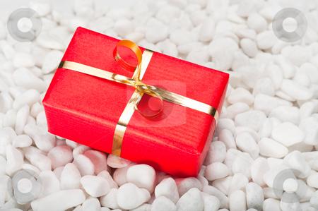 Gift Box on Stones stock photo, Small red and gold gift box on a background of white stones by Timothy Hodgkinson