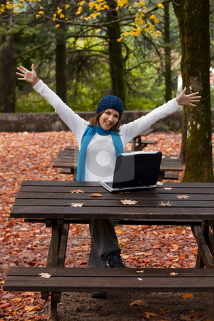 Happy work stock photo, Beautiful and happy young woman in the park in front of a laptop by ikostudio