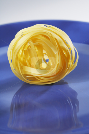 Tagliatelle stock photo, A Bunch of uncooked dried pasta tagliatelle on a blue plate by Stocksnapper