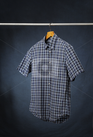 Summer shirt stock photo, A short sleeved men's plaid casual summer shirt hanging on a hanger. by Stocksnapper
