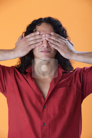Handsome man covering his eyes with his hands stock photo, Handsome curly haired man covering his eyes with his hands by Scott Griessel