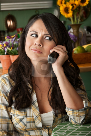 Frustrated Latina Woman on Phone stock photo, Frustrated Latina Woman on Phone  Waiting for Service or taking Sales call by Scott Griessel